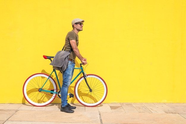 Side view of a young hipster man with a fixed bike