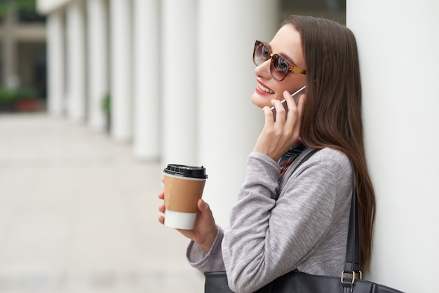 Side view of young lady in sunglasses making phone call leaning on building wall