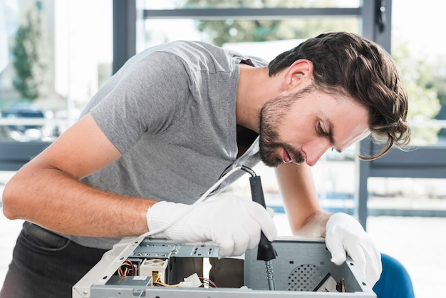 Side view of a young male technician working on broken computer