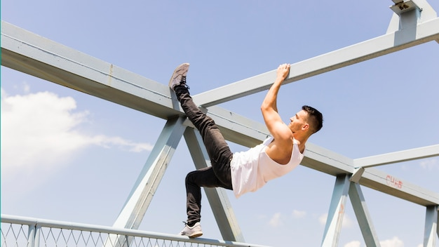 Side view of a young man climbing on the ceiling of a bridge