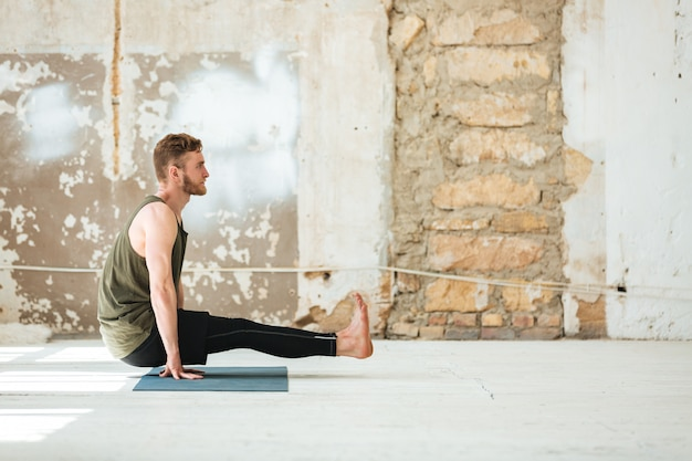 Side view of a young man doing yoga exercises