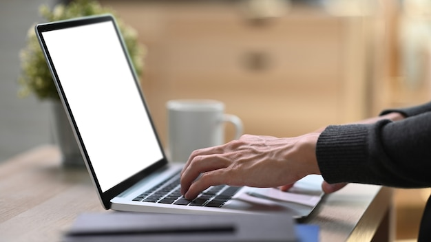 Side view of young man freelancer hands typing on keyboard of laptop computer.