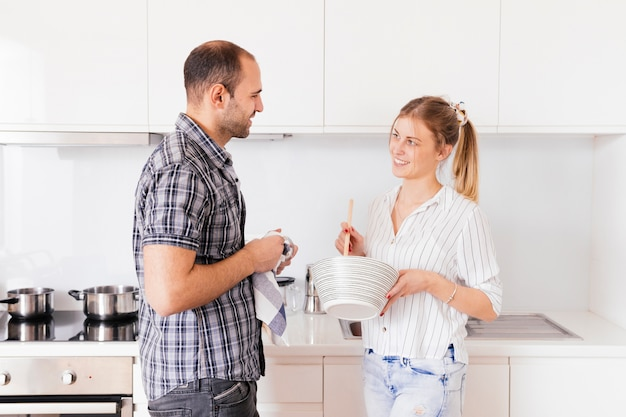 Side view of a young man helping his wife preparing food in the kitchen