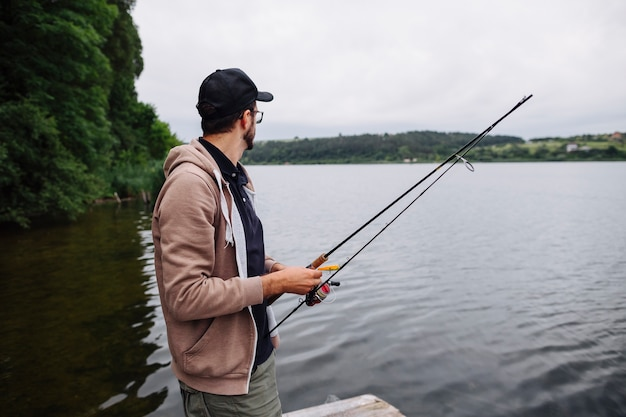 Side view of young man holding fishing rod