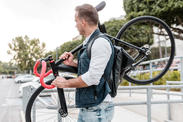彼の自転車を保持している側面図若い男