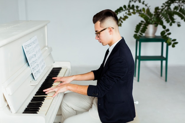 Side view of a young man playing grand piano