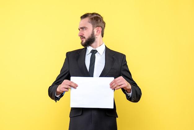 Vista laterale del profilo del giovane del giovane uomo d'affari che tiene documento in bianco sulla parete gialla