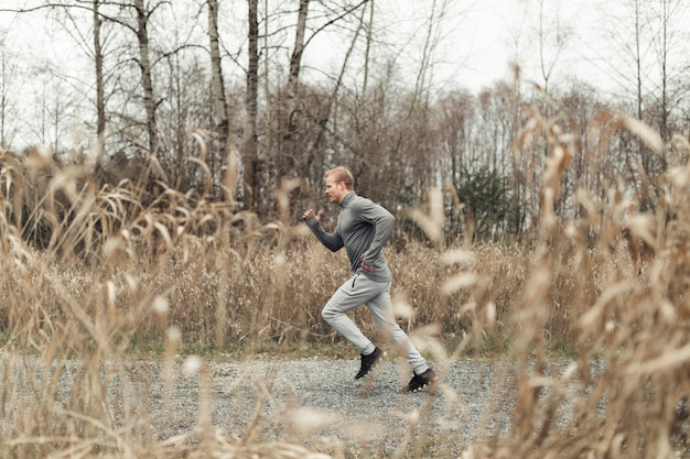 Side view of young man running in field
