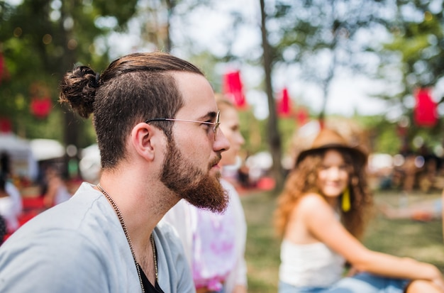 Side view of young man sitting at summer festival. copy space.