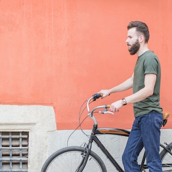 Side view of a young man standing with his bicycle