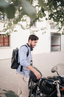 Side view of a young man standing with his motorbike