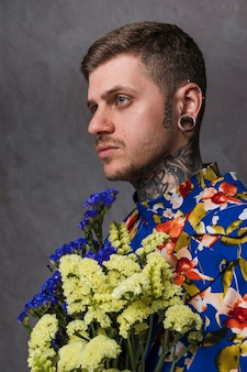 Side view of a young man with pierced ears and nose holding yellow and blue limonium flower against gray background