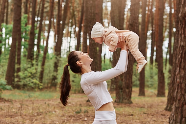 Side view of young mother throws up baby in air while happy family playing together in forest