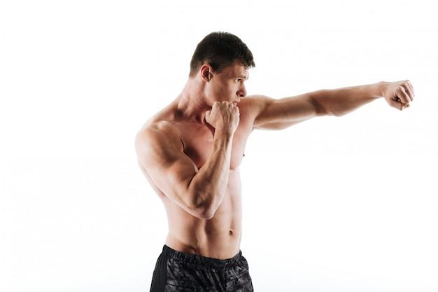 Vista laterale di giovane uomo muscolare di sport negli shorts neri che stanno nella posa di pugilato