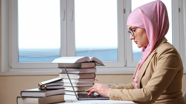 Side view of a young muslim woman in a pink hijab typing on a laptop among the stacks of books.