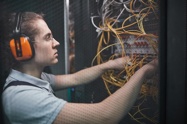 Side view of young network engineer connecting cables in server room during maintenance work in data center, copy space