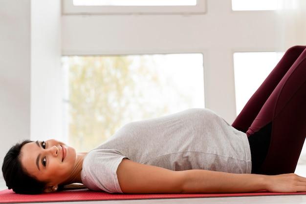 フィットネスマットで運動している若い妊婦の側面図