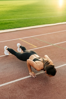 Side view of young slim attractive woman doing plank exercise at outdoor stadium basic workout
