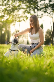Side view of young smiling woman training french bulldog in city park. purebred pet smelling treats from hand of female dog owner, beautiful summer sunset on background. animal training concept.