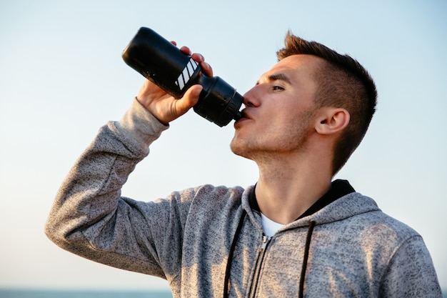 Side view of young sportsman drinking a water from bottle after running, workout