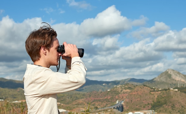 A side view of a young traveler from spain in a white shirt looking over mountains through binoculars