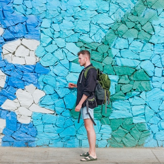 Side view of young traveler man carrying backpack against stone wall