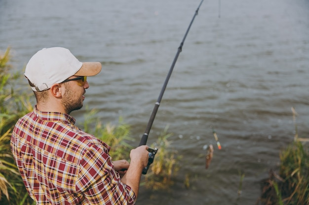 Side view young unshaven man in checkered shirt, cap and sunglasses pulls out fishing pole with caught fish on lake from shore near shrubs and reeds. lifestyle, recreation, fisherman leisure concept