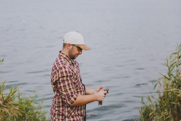 측면 보기 바둑판 무늬의 셔츠, 모자, 선글라스를 쓴 면도를 하지 않은 젊은 남자가 물고기를 잡고 물, 관목, 갈대 배경의 호숫가에 보유하고 있습니다. 라이프 스타일, 레크리에이션, 어부의 레저 개념