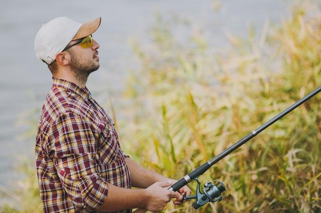측면 보기 바둑판 무늬 셔츠, 모자, 선글라스를 쓴 면도하지 않은 젊은 남자는 관목과 갈대 근처의 호숫가에서 낚싯대와 풀기 릴을 들고 있습니다. 라이프 스타일, 레크리에이션, 어부의 레저 개념.