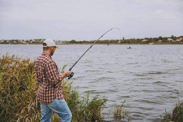측면 보기 바둑판 무늬 셔츠, 모자, 선글라스를 쓴 낚싯대를 든 젊은 남자가 관목과 갈대 근처 해안에서 호수에 낚싯대를 던집니다. 라이프 스타일, 레크리에이션, 어부의 레저 개념