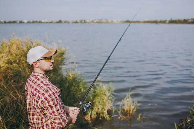 측면 보기 바둑판 무늬의 셔츠, 모자, 선글라스를 쓴 낚싯대를 든 면도를 하지 않은 젊은 남자는 관목과 갈대 근처 해안에서 호수에 있는 거리를 바라보고 있습니다. 라이프 스타일, 레크리에이션, 어부의 레저 개념.