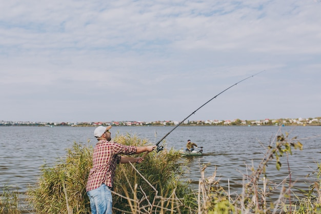 측면 보기 바둑판 무늬 셔츠, 모자, 선글라스에 낚싯대를 든 면도하지 않은 젊은 남자는 관목과 갈대 근처 해안에서 호수에 낚싯대를 던집니다. 라이프 스타일, 레크리에이션, 어부의 레저 개념.