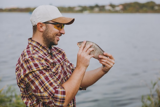 측면 보기 바둑판 무늬의 셔츠, 모자, 선글라스를 쓴 깎지 않은 젊은 남자는 물고기를 잡고 물, 관목, 갈대의 배경에 있는 호숫가에서 그것을 바라보고 있습니다. 라이프 스타일, 어부의 레저 개념