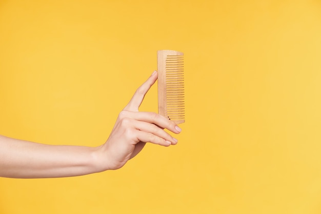 Side view of young well-groomed woman's hands keeping upright wooden while going to comb hair, isolated over orange background. haircare and human hands concept