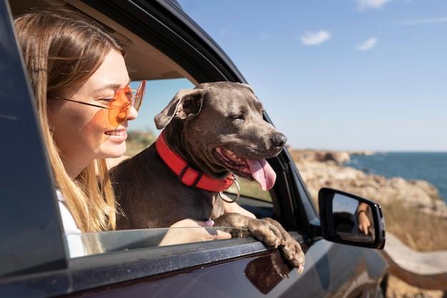 Вид сбоку молодая женщина и собака, отправляющиеся в поездку