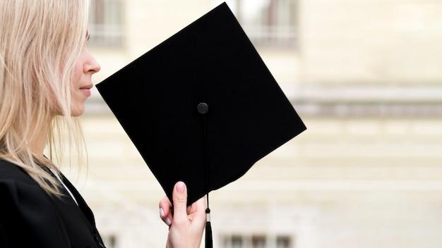 Вид сбоку молодая женщина празднует свой выпускной