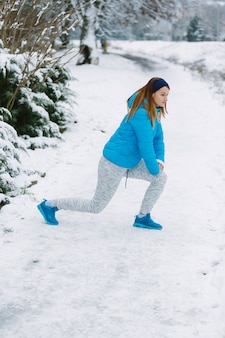 Side view of young woman doing exercise in winter