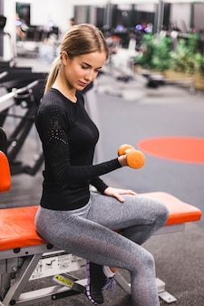 Side view of a young woman doing workout with dumbbell