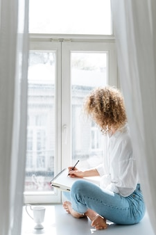 Side view of a young woman drawing at home near the window
