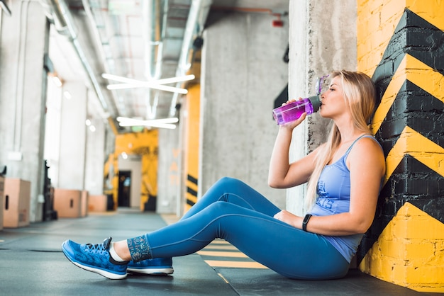 Side view of a young woman drinking water in fitness club