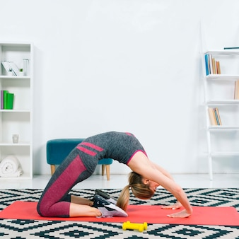 Side view of young woman exercising on red exercise mat over the pattern carpet at home