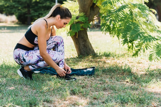 Side view of a young woman in the garden tying her shoelace