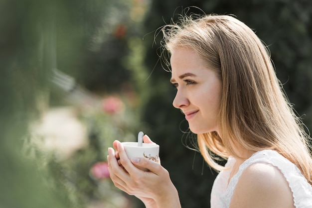 Side view of a young woman holding cup of coffee in two hands