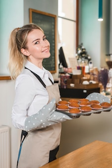 Side view of a young woman holding tray of fresh baked muffins