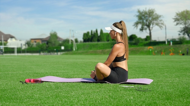 Side view of young woman listening to music, wireless headphobes stretching legs at stadium. stunning slim girl wearing sportswear practicing frog exercise in sunny summer day. flexibility concept.