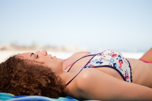 Side view of a young woman napping on a beach towel