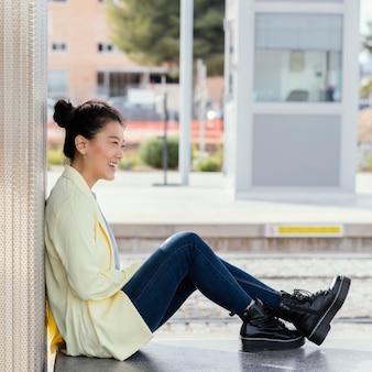 コーヒーを楽しんで屋外の側面図若い女性
