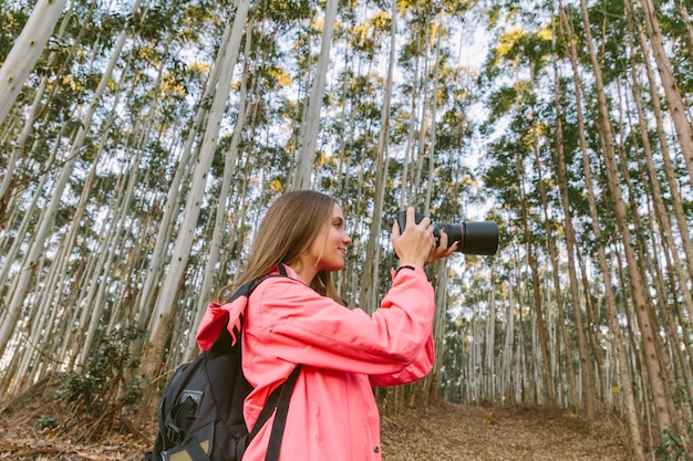Side view of a young woman photographing in forest
