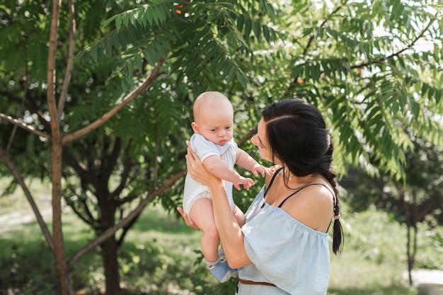 Vista laterale della giovane donna che gioca con il bambino nel giardino