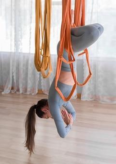 Вид сбоку молодая женщина, практикующая летать йогу, висит вверх ногами
